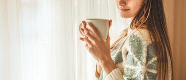 Cozy home. Woman with cup of hot drink by the window. Looking at window and drink tea. Good morning with tea. Young girl relaxing. Cozy home. Woman with cup of stock photo