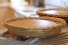 Cozy, homey image of two pumpkin pies cooling in a kitchen. Backlighting and shallow depth of field used. Image is in warm tones t. O enhance the ambience stock photo