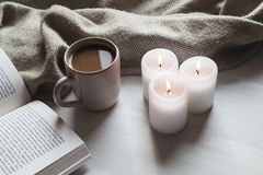 Cozy hot chocolate and book with candles and blanket. Mug of hot chocolate with three lit candles, an open book and a blanket on a wooden table. Hygge concept Stock Photo