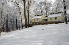 Cozy House on Snow Covered Hill. A cozy house atop a snow covered hill with snow covered trees Stock Image