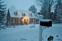Cozy house in the snow on a winter evening in December. Cozy Williamsburg-style house in the snow on a winter evening in December during the Christmas/Holiday Royalty Free Stock Photos