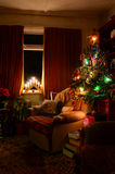 Cozy Indoor Christmas Tree Scene. A cosy indoor Christmas scene showing a comfy warm arm chair illuminated by festive lights and fairy lights on the Christmas Royalty Free Stock Image