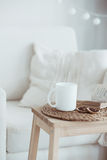 Cozy interior details. Still life interior details, cup of coffee and a book near white cozy chair Stock Photography