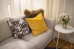 Cozy interior home design. Decorative pillows on light gray textile couch with white side table and flowers - cozy interior home design stock images