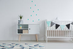 Mint water drop stickers. Cozy interior of kid`s bedroom with a mint water drop stickers on the wall, a plant standing on a cupboard, and a small bed for a baby royalty free stock images