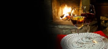 Cozy interior of a xmas evening. Two glasses of red white wine, fireplace chimney background. romantic xmas postcard. Copy space stock photography