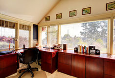 Cozy ivory office room wtih cherry wooden storage cabines Royalty Free Stock Photos