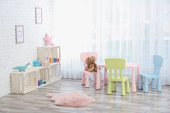 Cozy kids room interior with table, chairs. And toys royalty free stock image