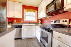 Cozy kitchen room with red wall and white cabinets Stock Image