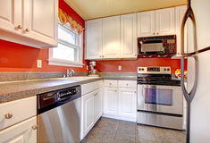 Cozy kitchen room with red wall and white cabinets Stock Photos