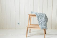 Cozy knitted scarf on a wooden ladder. Scandinavian style royalty free stock photo