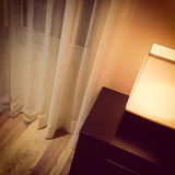 Cozy lamp in a room with white curtains Stock Image