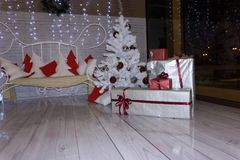 Cozy and light interior of the hous with a sofa and Christmas tree decorated with toys and gift boxes royalty free stock image