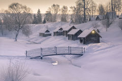 Cozy little houses on hill morning of winter village around frozen river Royalty Free Stock Photos
