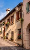 Cozy little street in Conegliano. Windows with blinds are decorated with flowers. The street rises steeply upwards Stock Photo