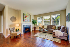 Cozy living room with fireplace, beige walls and hardwood floor Royalty Free Stock Photos