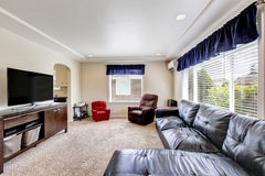 Cozy living room interior with black leather couch and tv set Stock Photos