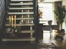 Cozy living room with stairs to second floor , winter decoration with burning candles on steps, window and cat. Winter holidays royalty free stock images
