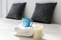Cozy look, candle and coffee mug on white towel Royalty Free Stock Photos