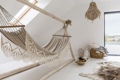 Cozy looking hammock. In a stylish day room with a big chandelier royalty free stock image