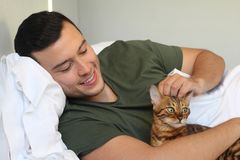 Cozy man in bed with his pet royalty free stock photos