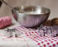 Cozy morning, family time, cooking in progress. Dough in a metal bowl, mixer, metal molds, rope for deciration, red and white tablecloth stock photo