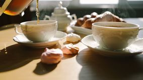 Cozy morning moment. tea is poured into cups from french press. Croissants and sweets. Sweet breakfast breakfast. Video. Ideal morning moment. tea is poured into stock video footage