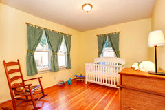 Cozy nursery room with crib and rocking chair Stock Images