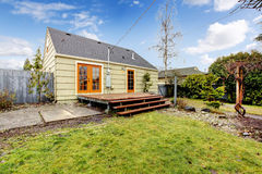 Cozy olive and orange house with backyard deck. Stock Photography