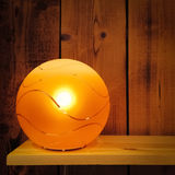 Cozy orange lamp on wooden shelf Stock Photo