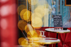 Cozy Parisian outdoor cafe with yellow lights and menu board on the table Royalty Free Stock Photos