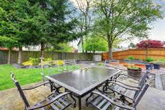 Cozy patio area with concrete floor and table set. Spacious backyard garden with green lawn royalty free stock image