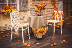 A cozy patio. Autumn leaves lying on the wooden floor, at the ce Royalty Free Stock Image