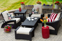 Cozy Patio Furniture on Luxury Outdoor Patio. Overview of Upscale Patio Set, Dark Wicker Luxury Furniture with Comfortable Cushions on Outdoor Stone Patio of Royalty Free Stock Photography