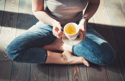 Cozy photo of young woman with cup of tea sitting on the floor Royalty Free Stock Image