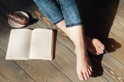 Cozy photo of young woman feet with book and cake on the floor Royalty Free Stock Images