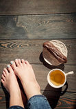 Cozy photo of young woman feet with tea and cake on the floor Royalty Free Stock Images