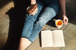 Cozy photo of young woman with tea and cake sitting on the floor Royalty Free Stock Image