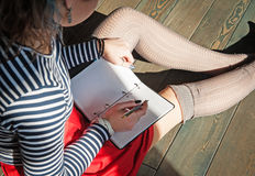 Cozy photo of young woman writing in notebook sitting on the flo Stock Photo