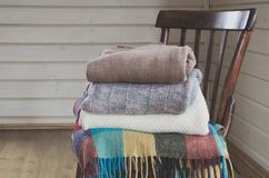 Cozy pile of warm clothes,sweaters on a vinatge wooden chair. Cozy pile of warm clothes, sweaters on a vinatge wooden chair Stock Image