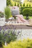 Cozy pillow with pattern and a pink blanket on a garden chair outside on a wooden terrace with rugs and plants stock photos
