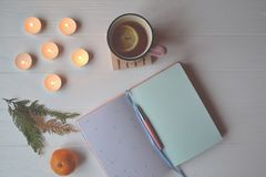Cozy place. Atmospheric workplace. A cup of tea, notebook and lighted candles. Cozy place for art. Atmospheric workplace. Stylish background with a cup of tea Stock Photos