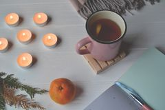 Cozy place. Atmospheric workplace. A cup of tea, notebook and lighted candles. Cozy place for art. Atmospheric workplace. Stylish background with a cup of tea Stock Images
