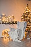 Christmas cozy place with a burning Christmas tree and white cha. A cozy place for Christmas photo shoots Royalty Free Stock Photography