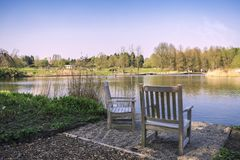 A cozy place. In the shade on the lake in the park for rest and contemplation Royalty Free Stock Photography