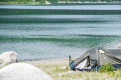 Mountain lake with a tourist tent on the beach royalty free stock images