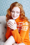 Cozy portrait of  woman in warm sweater on the bed with cup of t Royalty Free Stock Images