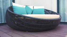 Cozy rattan sofa with cushions in lounge area on summer terrace luxury villa. Garden furniture for summer holidays on. Mainson veranda stock video footage