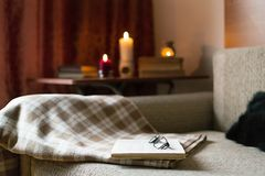 Cozy reading a book. Evening or morning time. Life style concept. A cozy sofa, a pillow and a plaid, open book and glasses. Leisure time, reading and resting stock images