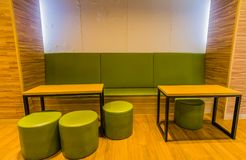 Cozy rest area with two wood top tables. And four round green stools and a long bench enclosed in a alcove with white wall and indirect lighting Royalty Free Stock Photo